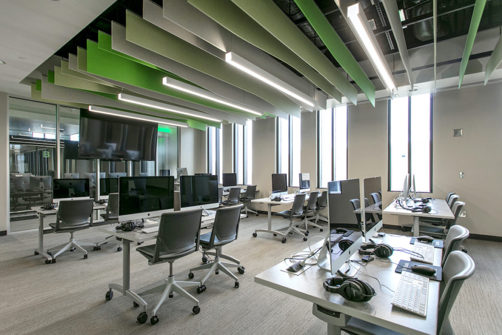Large office with beautiful green and white hanging ceiling panels and iMac workstations.
